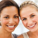 Brunette and blonde woman smile after receiving cosmetic dentistry in Cedar Park, TX, at Dental Salon