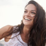 Brunette woman in a white tanktop smiles because she has good oral health and overall health