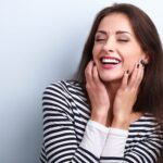 Brunette woman in a striped shirt smiles with her perfect smile after cosmetic dentistry