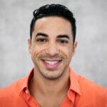 Brunette man in an orange shirt smiles after cosmetic dentistry in Cedar Park, TX